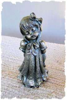 pewter figurine of a little girl day dreaming holding her hat behind