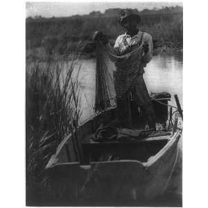 in boat holding fishing net,by Doris Ulmann,fishing
