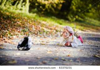 Cute Little Girl Falling Down And Crying In Autumn Park Stock Photo