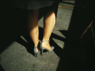 Legs of a Walking Woman Wearing Stockings and Gray High Heeled Shoes